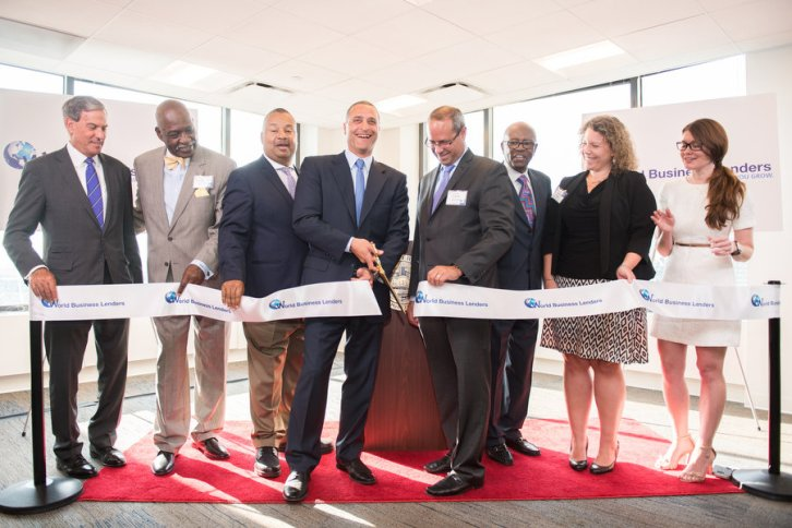 Doug Naidus, CEO of World Business Lenders, cuts the ribbon during the ceremony celebrating the relocation of WBL's corporate headquarters to 101 Hudson Street in Jersey City on Wednesday, July 20, 2016. He was joined by (left to right) Mitchell Rudin, CEO of Mack-Cali; Archbishop David J. Billings III of the United Fellowship of Churches International; U.S. Rep. Donald M. Payne Jr.; Deputy Mayor Marcos Vigil; former U.S. Rep. Ed Towns; Christina Fuentes with the N.J. Economic Development Authority; and Ward E Councilwoman Candice Osborne. Reena Rose Sibayan | The Jersey Journal