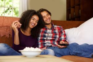 Smiling boyfriend and girlfriend relaxing watching tv